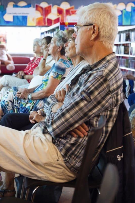 Senioren luisteren naar een seniorencollege van een studentdocent in een bibliotheek