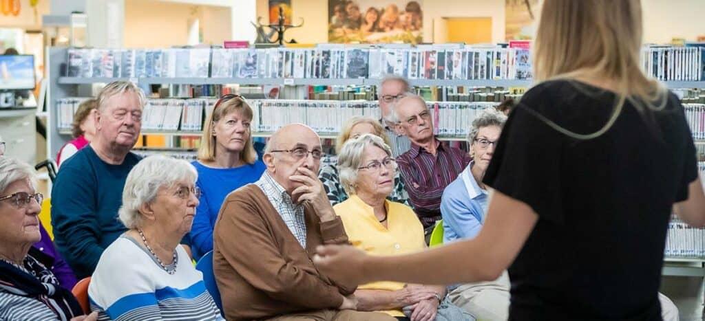 Senioren volgen een college van een studentdocent in een bibliotheek