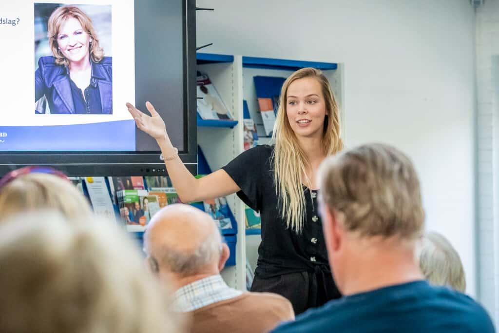Student geeft seniorencollege als studentdocent in een bibliotheek